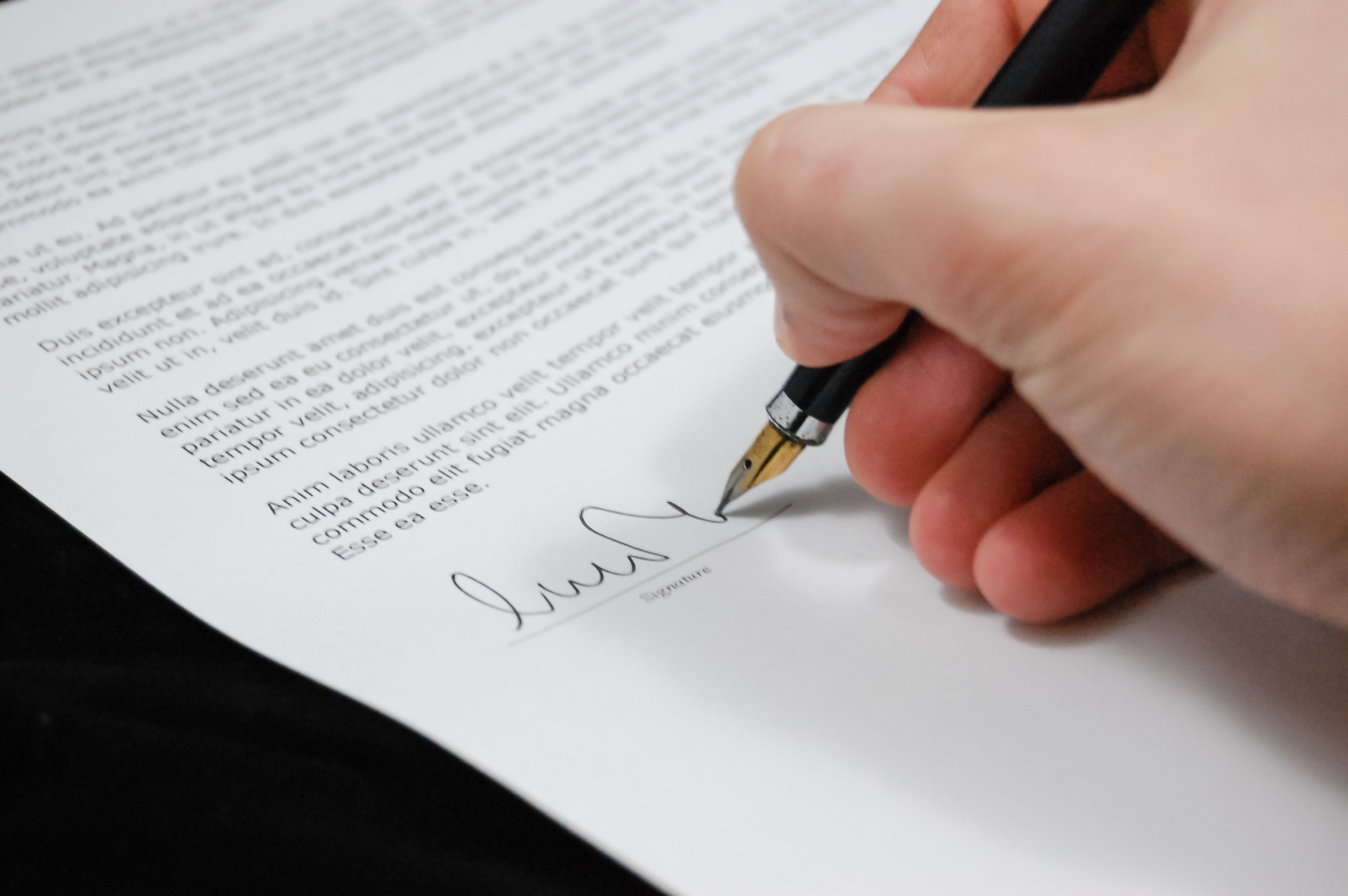 a close up of a person signign their name to a contract