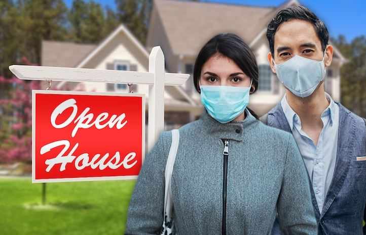 A couple in front of an Open House sign wearing face masks